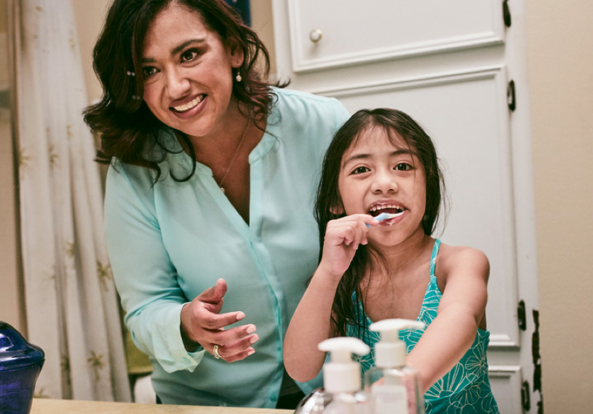 Girl With Mom Brushing her Teeth