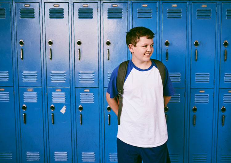 Boy Standing in Front of Blue Locker at School